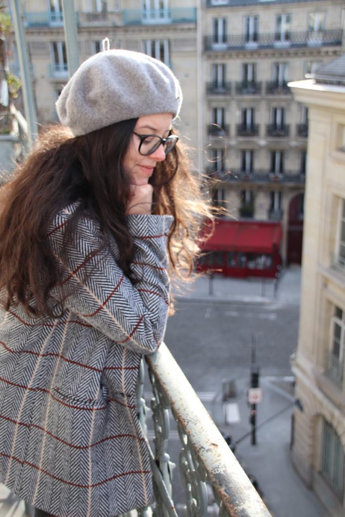 balcon avec vu sur le restaurant terra nova d' Emily in paris, dans une tenue avec une Veste Aly SAAJ et un béret C&A